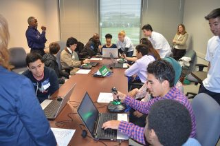 Vencore volunteer Johnny Martin (standing left) leads flight simulations for Thomas A. Edison AVID students at the Space Group STEM event on May 6, 2016.