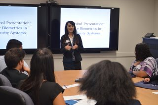 Vencore employee and recent George Mason graduate Gloria Rodriguez leads a biometrics presentation for students from the Thomas A. Edison AVID program at the Space Group STEM event on May 6, 2016.