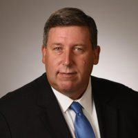 John P. Woods, Vice President & DHS Client Executive, CACI International, Inc.