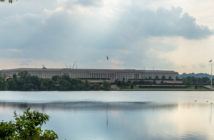 The Pentagon, headquarters of the Department of Defense, behind and reflected in the Pentagon Lagoon Yacht Basin with storm clouds developing in the sky and the sun's rays peeking through.