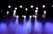 blurred theater stage with purple curtains and spotlights.