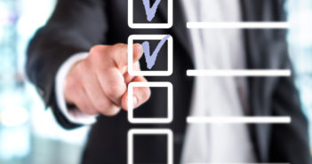 Business man with checklist and to do list. Man writing and drawing v sign check marks with hand and finger in square box. Project management, planning and keeping score of completed tasks concept. (Business man with checklist and to do list. Man writ