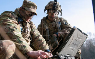 Sgt. 1st Class Joseph Rombold (left), an observer coach at Hohenfels Training Area, Germany, shows Spc. William Ritter (right), a military policeman with 287th Military Police Company, 97th Military Police Battalion, 89th Military Police Brigade, Fort Riley, Kansas, how to properly set up the system to operate the RQ-11 Raven, a small unmanned aerial system (sUAS), during Allied Spirit VIII at Hohenfels, Germany, Jan. 26, 2018. Roughly 4,100 troops from 10 nations are participating in Allied Spirit VIII, a multinational training exercise designed to test participants' readiness and capabilities. U.S. Army photo by Spc. Dustin D. Biven.
