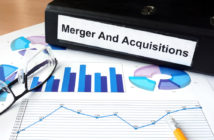 File folder with Merger and Acquisition and financial graphs. Business concept