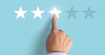 Hand choosing 3 stars rating on blue background - Average feedback on blue background