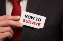 Businessman putting a card with text How to survive in the pocket