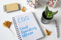 COO- Chief Operating Officer written in a notebook on white table