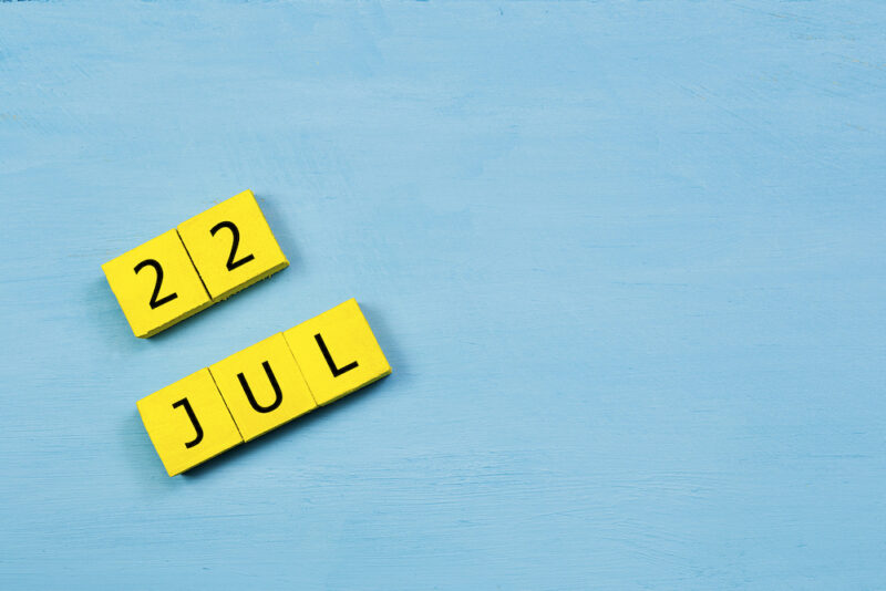JUL 22, yellow cube calendar on blue wooden surface with copy space