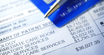 A hospital bill for$36,000 with a line item of various charges is photographed with a very shallow depth of field. A credit card and a ballpoint pen rest out of focus in the background. (A hospital bill for$36,000 with a line item of various charges i