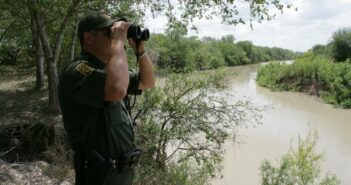 In this file photo from 2016, a Border Patrol agent scans the area into Mexico with binoculars. Photo: USBP