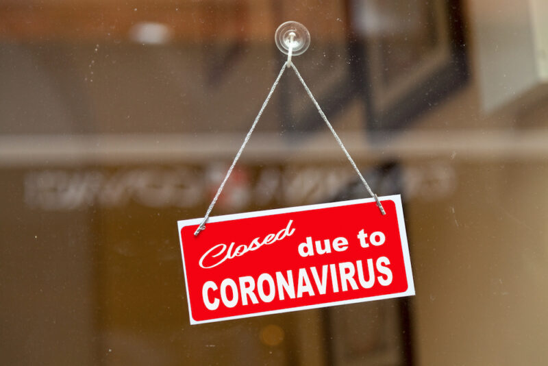 """Red sign hanging at the glass door of a shop saying """"Closed due to coronavirus""""."""