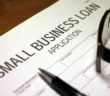 Someone filling out Small Business Loan Application.