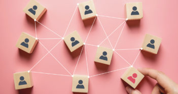 Building a strong team, Wooden blocks with people icon on pink background, Human resources and management concept.