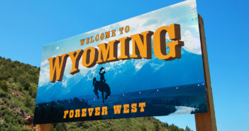 "Welcome to Wyoming sign with text ""Forever West"" and horse with cowboy"