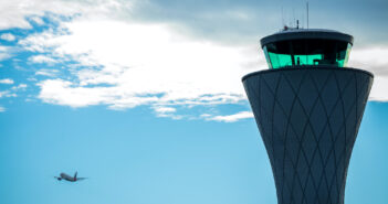 airport control tower with airplane flying in the sky after takeoff. Image: gonzalo martinez/iStock