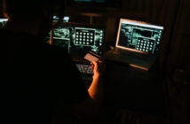 Hacker using laptops in the dark room and stealing credit card information