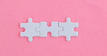Three white jigsaw pieces on pink background.