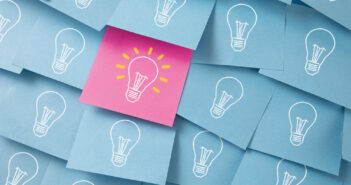 Many light bulbs drawn on blue and pink adhesive notes.