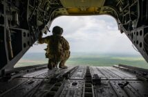 A U.S. Soldier kneels at the back of a CH-47 Chinook helicopter on the way to Qayyarah Airfield West, Iraq, March 26, 2020. (U.S. Army photo by Spc. Angel Ruszkiewicz)