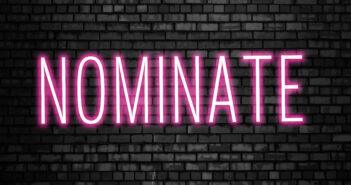 Nominate glowing pink neon sign on black brick wall. Business winner achievement concept for Election Nomination. Image: ANA BARAULIA