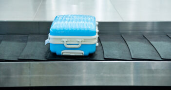 Blue suitcase on conveyor belt in the airport.